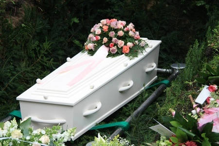 11194233 - white coffin and several sympathy floral arrangement on a grave side