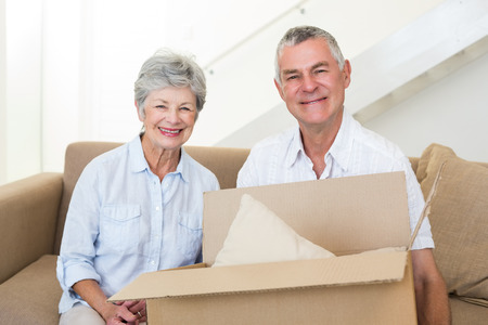 27195493 - cheerful senior couple moving into new home smiling at camera